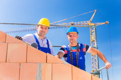 Bouwwerfarbeiders die huis met kraan bouwen Royalty-vrije Stock Fotografie