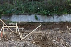 Bouwwerfmening van concrete behoudende muur op helling achter gegraven positie en rebar Stock Foto