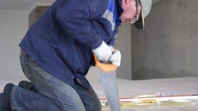Bouwwerkzaamheid - een mens die gezaagde houten vloerraad zagen stock video