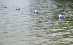 Bouys fäste samman med ett rep på vatten Royaltyfria Bilder