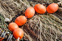 Bouys on Nets. A pile of grey fishing nets and on top several orange buoys in the harbour of Urk, Flevoland, The Netherlands royalty free stock photography