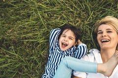 Boven bebouwd beeld van het gelukkige mooie vrouw lachen en het spelen met haar leuk meisje op groen gras openlucht loving royalty-vrije stock afbeeldingen