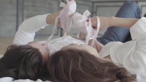Boven geschoten gelukkig paar die in bed het spelen met het close-up van roze kinderen liggen pointe Jonge familie die op a wacht stock footage