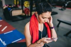 Boven geschoten portret van een mooie sportieve jonge vrouw die aan muziek die van haar smartphone binnen luisteren, een onderbre stock foto's