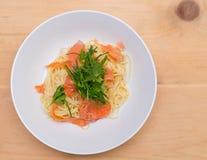 Boven geschoten van een gerookte zalmspaghetti met verse kruiden stock fotografie