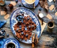 Boven geschoten van eigengemaakte yummy chocolade bevindt de wafels zich op uitstekende platen met blauw ornament op houten donke stock afbeelding