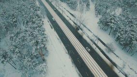 Boven hoogste mening over de winter bosweg met auto's en tram Lengte van de sneeuwval de luchthommel stock video