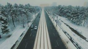 Boven hoogste mening over de winter bosweg met auto's en tram Lengte van de sneeuwval de luchthommel stock footage