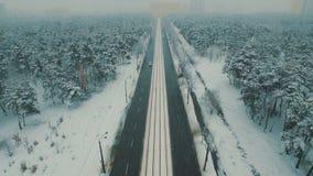Boven hoogste mening over de winter bosweg met auto's en tram Lengte van de sneeuwval de luchthommel stock videobeelden