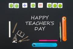 Boven kantoorbehoeftenlevering en dag van de tekst de gelukkige leraar ` s op zwarte achtergrond royalty-vrije stock fotografie