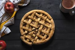 Boven mening van rustieke keuken sneed een lijst met een appeltaart met één plak, handdoek, appelen, en hete chocolade Traditione stock foto
