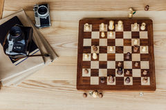Boven mening van schaakraad met oude uitstekende camera's en boeken wordt geplaatst dat royalty-vrije stock afbeelding