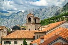 Boven rode daken van historische stad Kotor met torensst Tryphon Kathedraal, betrekken Montenegro en het landschap op achtergrond Stock Afbeeldingen