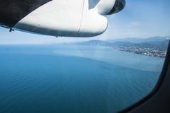 Boven wolken, overzeese kust, bergen en hemel zoals die in venster van het schroefplan wordt gezien Royalty-vrije Stock Fotografie