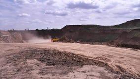 Bovengrondse mijnbouwsteengroeve met machines op het werk en vliegend stof op bewolkte hemelachtergrond, zware industrieconcept s stock video