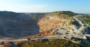 Bovengrondse mijnbouwsteengroeve met partijenomachinery op het werk stock footage