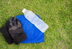 Bovenkant - de fles van het meningswater met Geschiktheidshandschoenen en handdoek met gras Stock Afbeelding