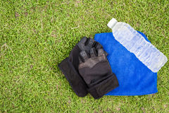 Bovenkant - de fles van het meningswater met Geschiktheidshandschoenen en handdoek met gras Royalty-vrije Stock Afbeeldingen