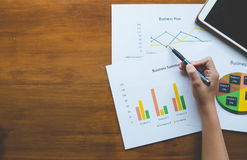 Bovenkant - mening van de pen van de handholding met Bedrijfssamenvatting of het rapport van het businessplan met Grafieken en gr royalty-vrije stock fotografie