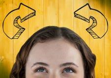 Bovenkant van het hoofd die van de vrouw omhoog grijze gebogen pijlen tegen geel houten paneel bekijken Stock Afbeelding