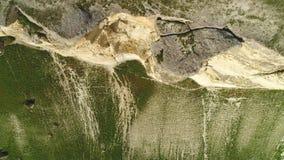 Bovenkant van hoge witte die klippenhelling met stenen en bodem van de klip met groen gras wordt behandeld schot Luchtmening van stock footage