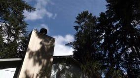 Bovenkant van huis met bomen en wolken die over het blazen stock footage