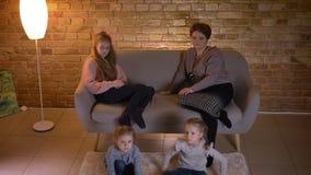 Bovenkant van Kaukasische moeder met drie dochters wordt geschoten die op bank en het letten op film aandachtig in comfortabele h stock footage