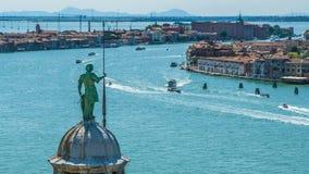 Bovenkant van klokketoren met het standbeeld van Heilige George in Venetië, verkeer op Grand Canal, reis stock footage