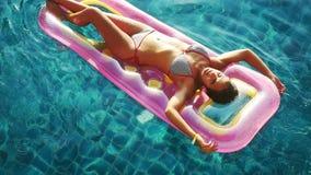 Bovenkant van mening van jonge aantrekkelijke glimlachenvrouw die van de zomer op opblaasbare matras in glashelder water in het z stock footage