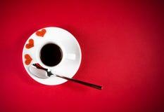Bovenkant van mening van decoratieve rode harten dichtbij kop van koffie op rode lijst, de dag van de conceptenvalentijnskaart Stock Fotografie