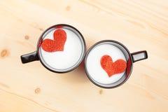 Bovenkant van mening van koppen van melk met decoratief hart op houten lijst, concept valentijnskaartdag Stock Foto's