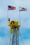 Bovenkant van Olie Rig Displaying de V.S. en de Vlag van de Staat van Californië stock foto