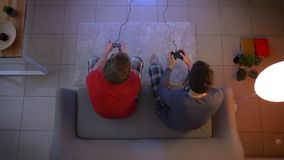 Bovenkant van twee vrienden die in pyjama's wordt geschoten videospelletje spelen die samen bedieningshendel emotioneel in de woo stock video