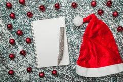 Bovenleer, bovenkant, mening van hierboven van een blocnote, houten uitstekende pen, altijdgroen rood speelgoed, Kerstmanhoed op  royalty-vrije stock foto