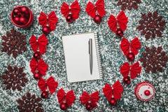 Bovenleer, mening van hierboven van een blocnote en pen, binnen van een cirkel van rode bogen, altijdgroen speelgoed wordt gecree Royalty-vrije Stock Afbeelding