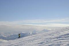 Bovenop de wereld De skiër gaat tot de bovenkant van de berg Boven de wolken royalty-vrije stock foto's