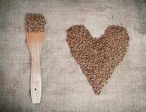 Bovete med träskoveln som ligger på kanfas formad hjärta royaltyfri fotografi