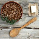 Bovetehavregröt med smör i en lerabunke mot en träbakgrund Begrepp: vegetarisk mat, sund matlagning royaltyfri bild
