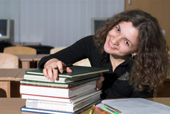 Bow above the books. Young female student is putting hand on stack of books Royalty Free Stock Photography