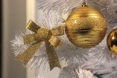 Bow and ball for decoration of gold color with sequins on a white Christmas tree. Christmas preparations, home decoration. stock photography