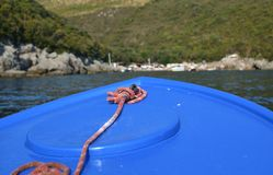 Bow of a blue boat. Approaching a hill with a beach in summer Stock Photos