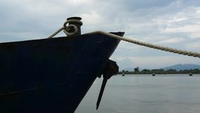 Bow of blue metal ship with rusty anchor moored at dock at sunset. stock footage