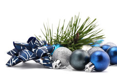 Bow with blue and silver Christmas ornaments. Fancy bow with blue and silver Christmas ornaments and a pine twig isolated on white background. Shallow dof stock photos
