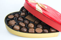 Bow, box and chocolates. Red heart box, gold bow and chocolates Stock Photography