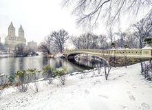 Bow bridge Central Park during snow storm. The Bow Bridge  is a cast iron bridge located in Central Park, New York City, crossing over The Lake Royalty Free Stock Image