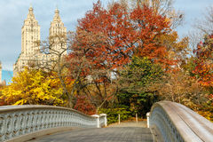 Bow Bridge and fall colors in Central Park, Manhat. Display of autumn colors by the Bow Bridge in Central Park, with Upper West Side building behind the trees Royalty Free Stock Image
