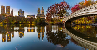 Bow Bridge at New York Central Park. Panorama of Bow Bridge with buildings reflected in the lake during Dusk stock photography