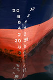 Bow of the cargo ship with draft scale numbering. Bow of the cargo ship with red waterline and draft scale numbering Stock Photos