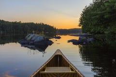 Bow of a cedar canoe at sunset - Haliburton, Ontario, Canada. Bow of a cedar canoe on a lake at sunset - Haliburton, Ontario, Canada royalty free stock images