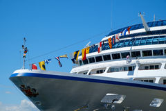 Bow of cruise ship at dock. Seattle, WA, USA July 15, 2016: Bow of Oceania Cruise ship Regatta with colorful flags and worker doing maintenance work outside of Stock Images